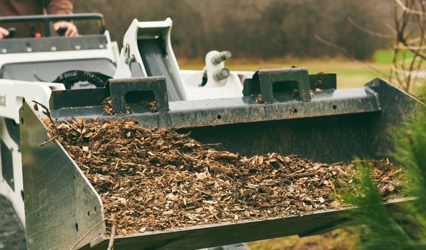 Independent Tree employee moving wood chip mulch with a front loader